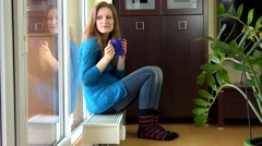 Happy woman with warm clothes drink tea and dream sitting on warm radiator Stock Footage