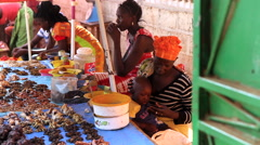 Mother taking care of child during street seller job - Africa city market Stock Footage