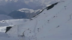 Ski slopes arranged in high mountains with grows cliffs where plenty of athle Stock Footage