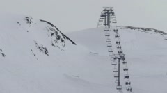 Skiers coming down a steep slope while other skiers on a chairlift lead on th Stock Footage