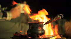 Cezve with hot coffee (tea) on the campfire. Man hands with cup in defocus. Stock Footage