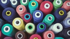 Row of colorful thread spools on table. Bright colors Stock Footage