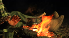Man warming hands and waiting for coffee (tea) near the campfire. Stock Footage