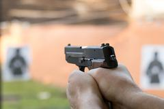 Shooting with a pistol. Man aiming pistol in shooting range. Stock Photos