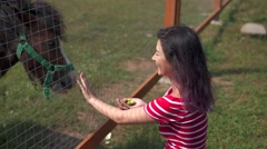 Attractive woman feeding a pony in farm Arkistovideo