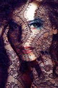Portrait of beauty young woman through lace close up mistery makeup Stock Photos