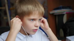 The child listens to music on smartphone in the headphones and hops head in home Stock Footage