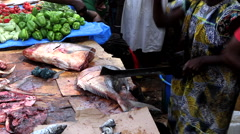 Woman fishmonger slicing fish with knife - city market Bandim Guinea Africa Stock Footage