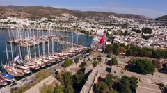 Turkish flag castle marina aerial yacht drone shot business boat harbor Bodrum Stock Footage