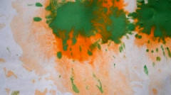 Colored paint splashes on white wet paper Stock Footage