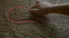 Drawing heart in flax seeds, slow motion Stock Footage