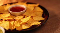 Closeup of a black plate with nachos and tomato sauce over fireplace Stock Footage