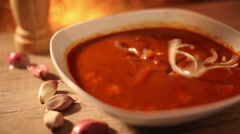 A white bowl of tomato soup with onion rings standing on a wooden table and g Stock Footage