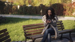Beautiful girl on a bench in your phone looking photos. Cool autumn park Stock Footage