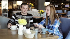 Boy and girl in cafe. People use laptop and smartphones, talk and drink coffee. Stock Footage