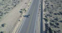 Motorcycle rider on a lonely highway in the desert Stock Footage