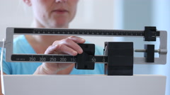 Woman weighing herself on scale Stock Footage