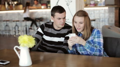 Woman and Man sitting in cafe talking and looking at phone in hand Stock Footage