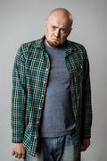 Resentful sad emotive man in shirt posing over beige background Stock Photos