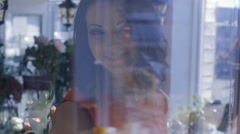 Girl smiling and looking through the window of the flower shop Stock Footage