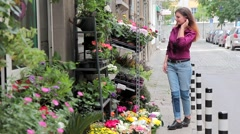 A young girl chooses flowers in a flower shop on the street Stock Footage
