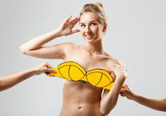 Hands covering blonde girl with yellow swimwear over white background Stock Photos