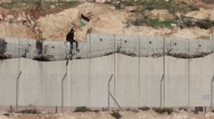 Palestinian Boy sticks flag on Security fence Stock Footage