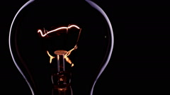 Loop of flashing electrical bulb on black background / switch on and switch o Stock Footage