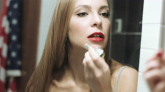 Beautiful blond woman paints her lips Stock Footage