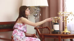 Young beautiful woman sitting on chair, talking on vintage phone, Stock Footage