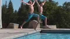Two boys jumping into pool in super slow motion Stock Footage