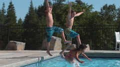 Three kids jumping into pool in super slow motion Stock Footage