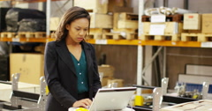 4k, Tired businesswoman with a concerned look working at a large warehouse. Stock Footage