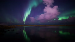 Deeply colorful aurora borealis night sky reflecting calm lake water Iceland 4k  Stock Footage