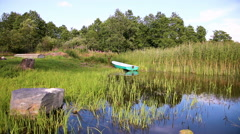 Fishing boat moored on the lake in the morning in summer sunny day. Summer's  Stock Footage