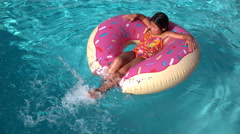 Girl splashing feet on inflatable doughnut in super slow motion Stock Footage