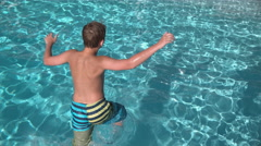 Boy jumping into pool in super slow motion Stock Footage