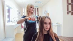 Hair stylist makes professional hairstyle of young woman using curling irons in Stock Footage