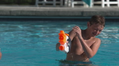 Boys having squirt gun fight in pool, super slow motion Stock Footage