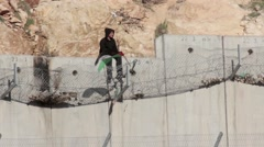 Palestinian Boy sitting on Security fence with flag Stock Footage
