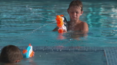 Boy squirting water gun in pool, super slow motion Stock Footage