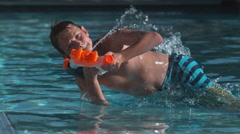 Boy dives into pool shooting water gun,  super slow motion Stock Footage