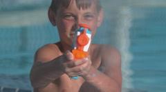 Closeup of boy spraying water gun in super slow motion Stock Footage