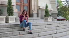 Young woman sitting on stairs at entrance to building and looking at smartphone Stock Footage