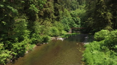 Flying over a creek with bridge, Oregon, USA Stock Footage