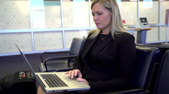 Business woman using laptop computer at airport Arkistovideo