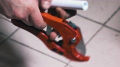 Man Uses a Cutting Tool for Cut of Polypropylene Pipes Stock Footage