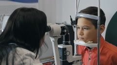 Boy checks colour eyesight at the reception of an ophthalmologist. Stock Footage