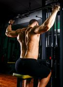 Power athletic guy bodybuilder, execute exercise with gym apparatus, on broadest Stock Photos