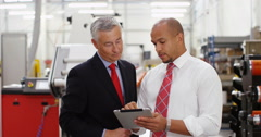 4K Business partners in factory looking at tablet & discussing operations Stock Footage